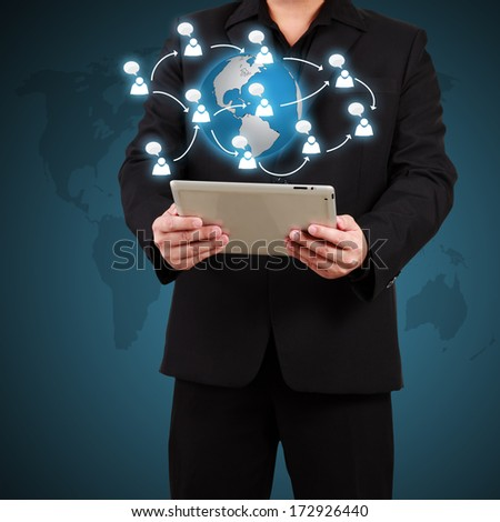 Businessman holding a tablet with globe and community icons. Concept of business communication.