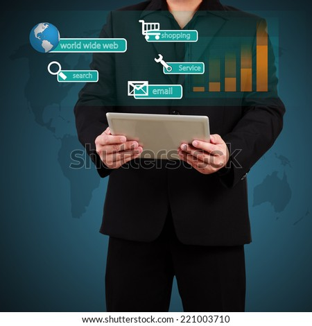Businessman holding a tablet with globe and community icons. Concept of business communication. - stock photo