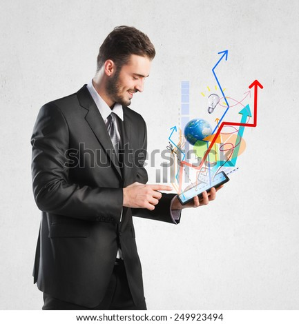Businessman holding a tablet with growing graphics - stock photo