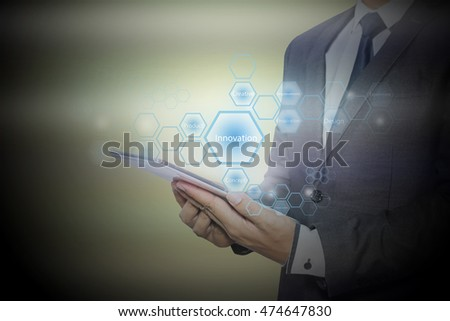 Businessman holding a tablet with innovation words cloud on the screen. business concept.