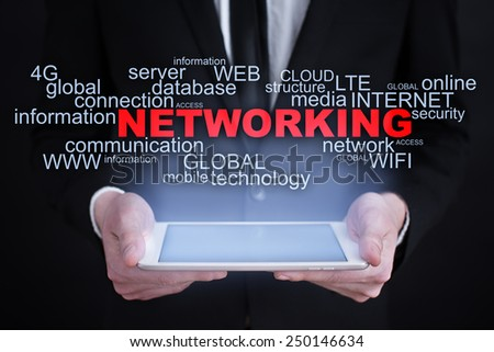 Businessman holding a tablet with networking words cloud on the screen. business  concept. - stock photo