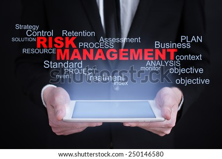 Businessman holding a tablet with risk management words cloud on the screen. business   concept