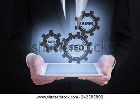 businessman holding a tablet with the projection of internet marketing concept. online marketing. digital marketing. SEO, SEM, SMM. - stock photo