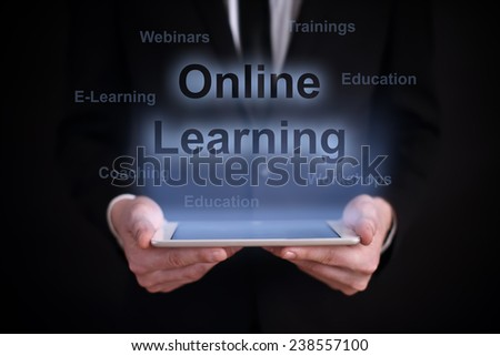 """Businessman holding a tablet with the projection """"online learning"""" over the screen. Internet and education concept. Business concept - stock photo"""