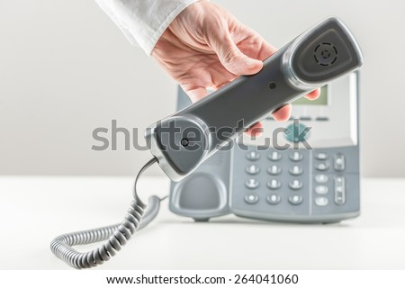 Businessman holding a telephone handset in front of the instrument on a white desk or table in a communication and contact concept. - stock photo