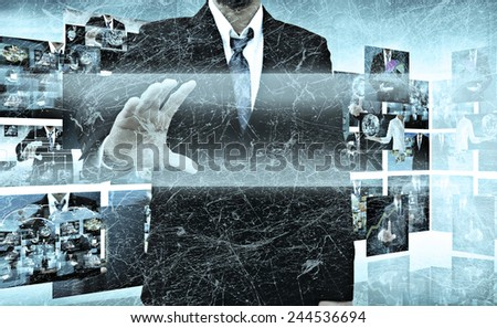 businessman holding a touch screen interface in the old texture - stock photo
