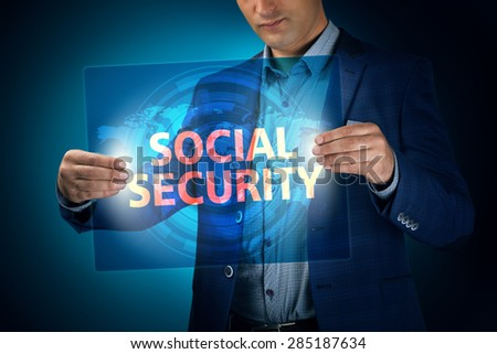 Businessman holding a transparent screen with an inscription a social security. Business, technology, internet and networking concept. - stock photo