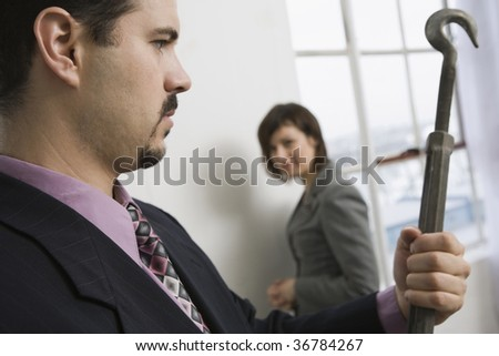 Businessman holding a turnbuckle with a businesswoman in the background - stock photo