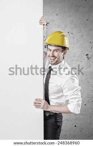 Businessman holding a white banner in front of a concrete wall - stock photo