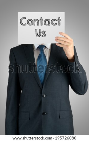 businessman holding a white sheet of paper with the inscription on grey background: contact us - stock photo