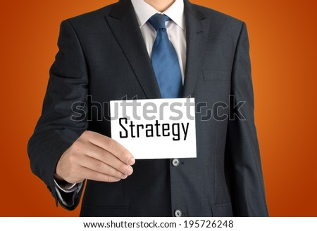 businessman holding a white sheet of paper with the inscription on nice warm orange background: strategy - stock photo
