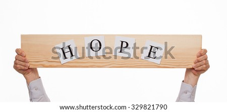 "Businessman holding a wooden plate with an inscription ""Hope"", white background"
