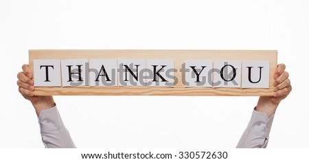 """Businessman holding a wooden plate with an inscription """"Thank you"""", white background - stock photo"""