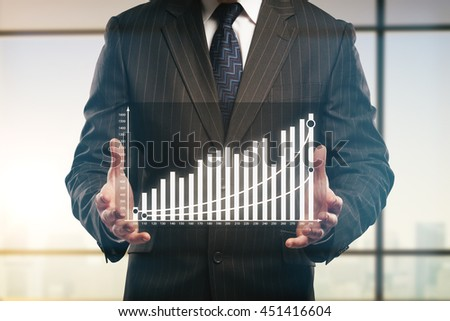 Businessman holding abstract business chart on blurry window background - stock photo