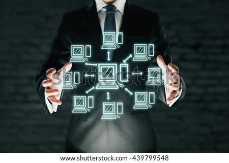 Businessman holding abstract computer network on dark brick background - stock photo