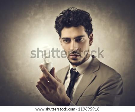 Businessman holding an energy saving lamp - stock photo