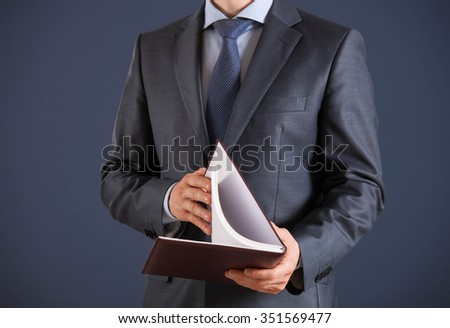 Businessman holding an opened book, dark background