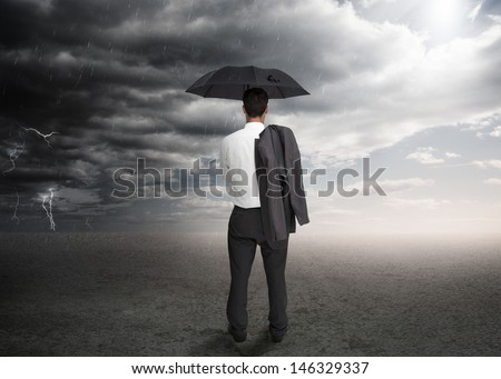 Businessman holding an umbrella and a jacket over his shoulder facing a storm