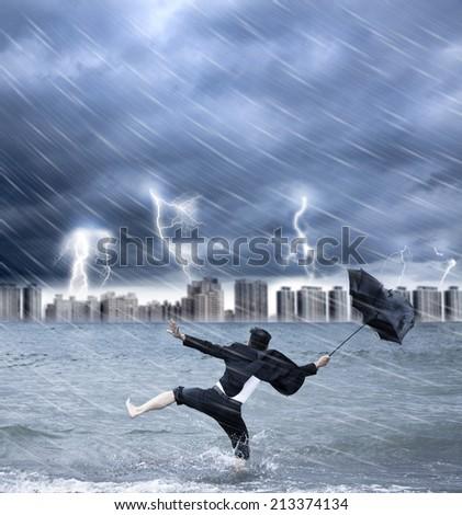 businessman holding an umbrella with thundershower - stock photo