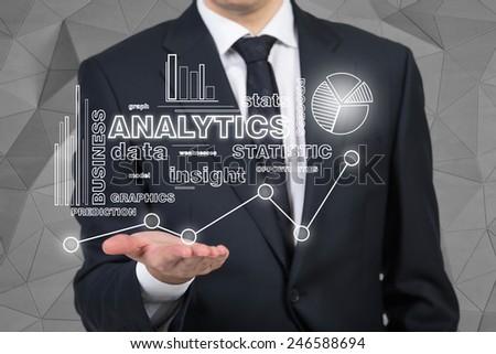 businessman holding analytics symbol on black background - stock photo