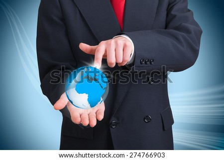 businessman holding and pointing to a terrestrial globe