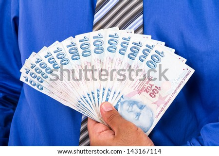 Businessman holding and showing one hundred Turkish liras banknotes. - stock photo