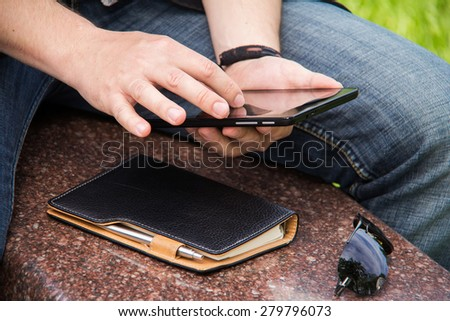 Businessman holding and touching on touch screen digital tablet in the park
