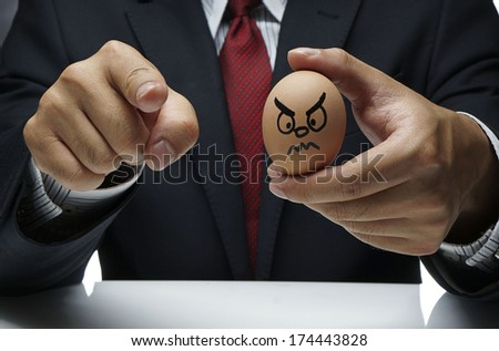 Businessman holding Angry Egg character and other finger pointing at the camera - stock photo