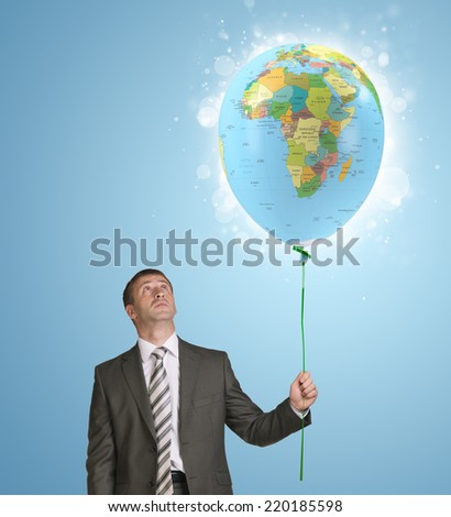 Businessman holding balloon with the image of world map