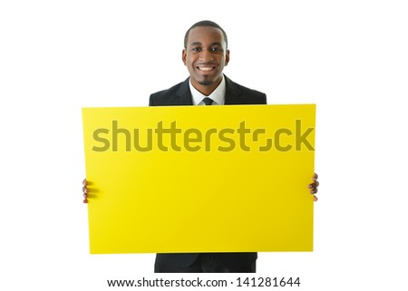 Businessman holding big yellow board to be filled in with ideas or concepts - stock photo