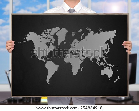 businessman holding blackboard with drawing world map - stock photo