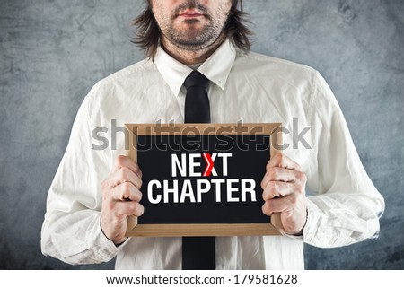 Businessman holding blackboard with NEXT CHAPTER title. Advance in business. - stock photo