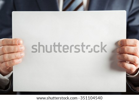Businessman holding blank paper, copy space - stock photo