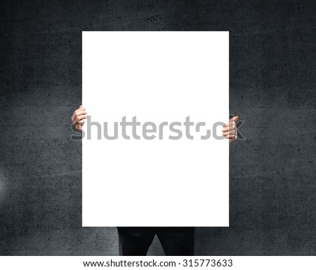 businessman holding blank poster in hand.