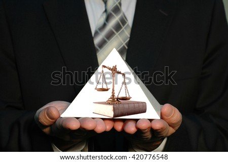 Businessman holding blank pyramid whit scales of justice on the book - stock photo