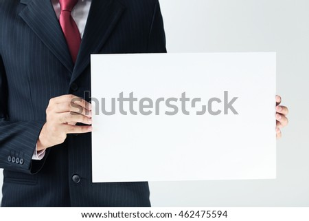 Businessman holding blank sheet of paper in his hands