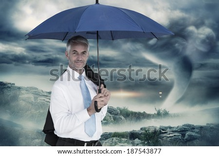 Businessman holding blue umbrella against stormy sky with tornado over landscape