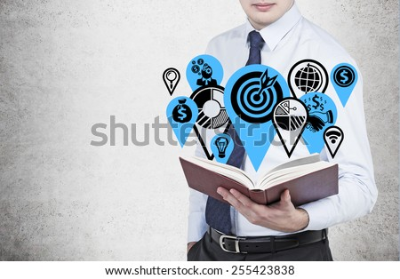 businessman holding book with business icons - stock photo