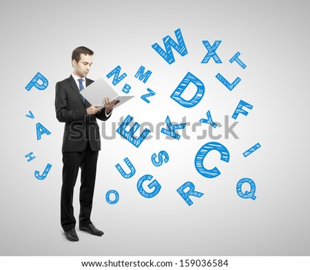 businessman holding book with many letters on gray background