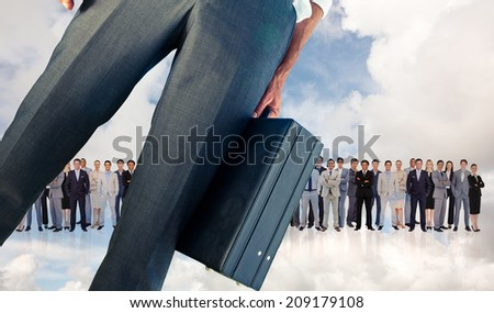 Businessman holding briefcase against blue sky with white clouds and business people - stock photo