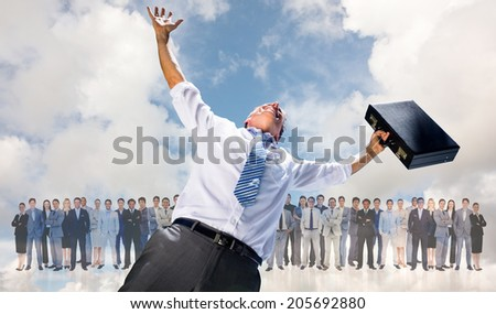 Businessman holding briefcase and cheering against blue sky with white clouds - stock photo
