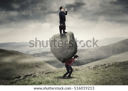 Businessman holding briefcase and shouting using his hand while standing on the stone and partner with blue sky in the background