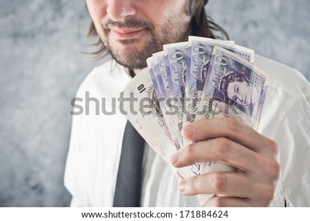 Businessman holding British pounds money. Paying with British currency. - stock photo