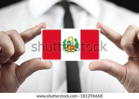 Businessman holding business card with Peru Flag - stock photo