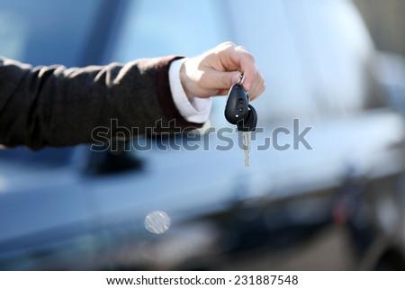 Businessman holding car key outdoors - stock photo