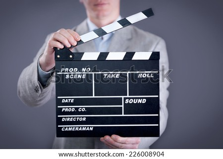 businessman holding clapper board on gray background