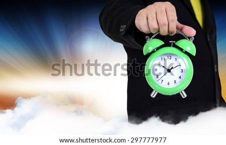 businessman holding clock on abstract background