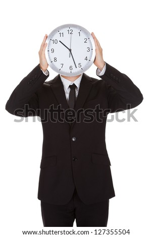 Businessman holding clock over the face. Isolated on white