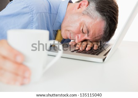 Businessman holding coffee and sleeping on his laptop on his desk - stock photo