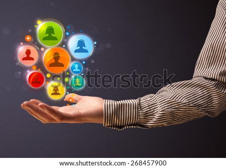 Businessman holding colorful social network icons in his hand - stock photo